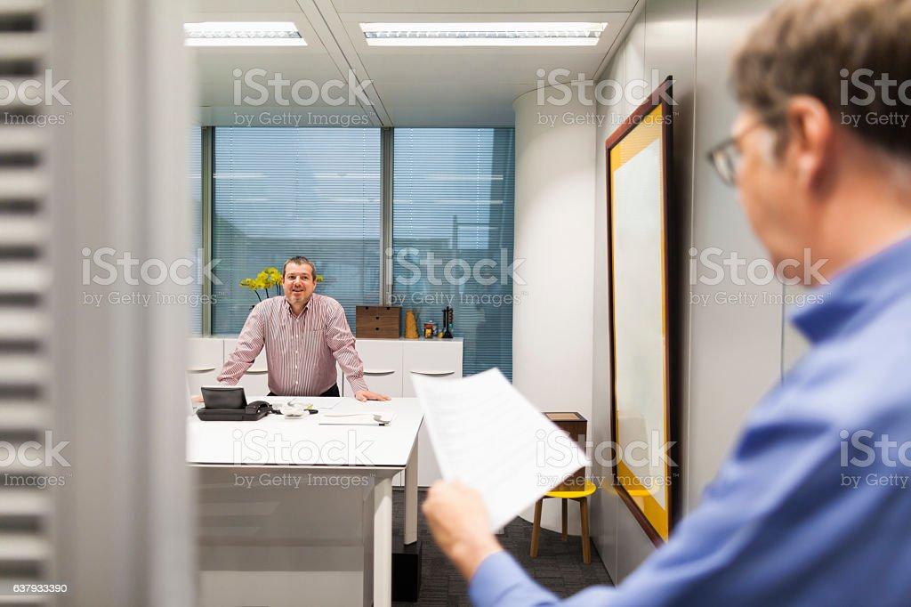 Businessmen talking in office stock photo