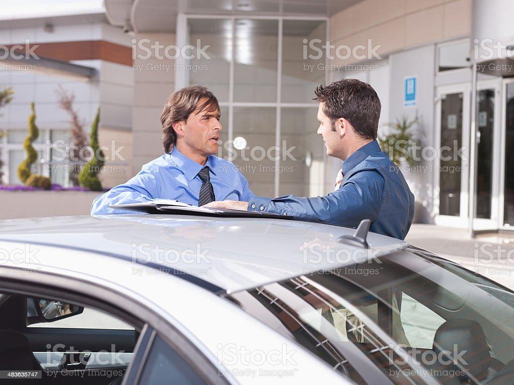 Businessmen talking near car stock photo