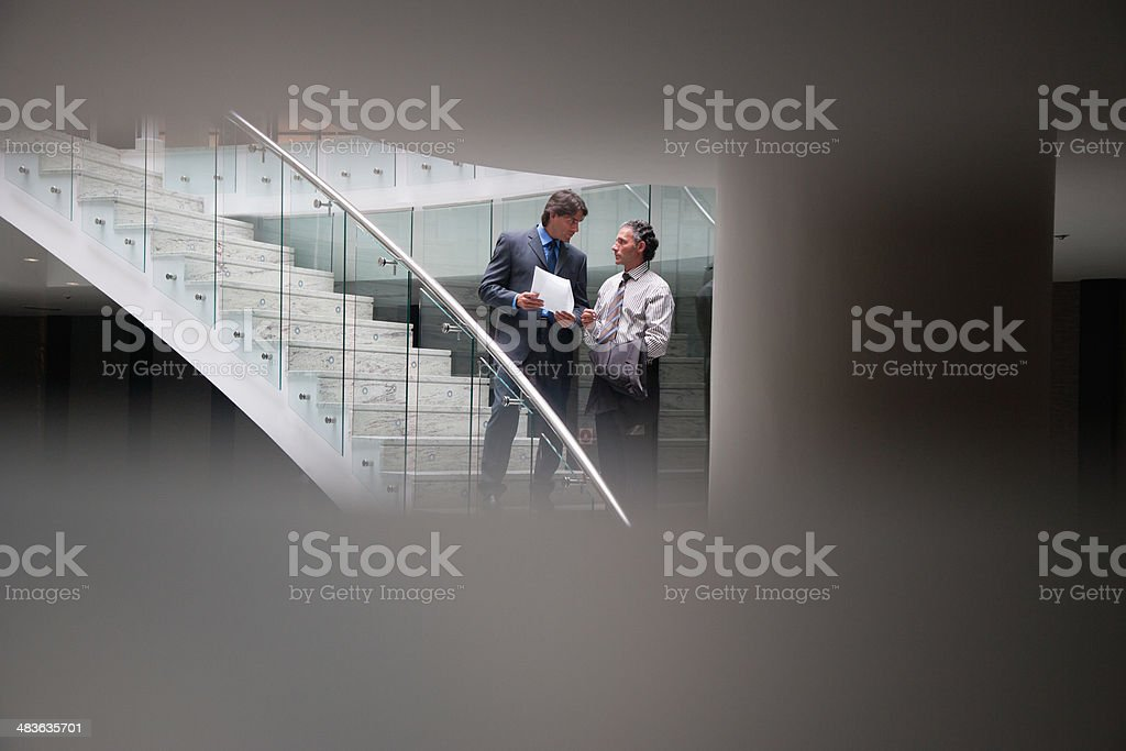 Businessmen talking on staircase stock photo
