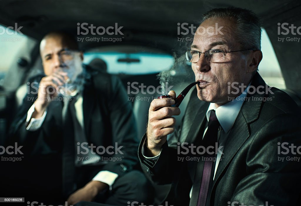 Businessmen traveling in a limousine and smoking. stock photo
