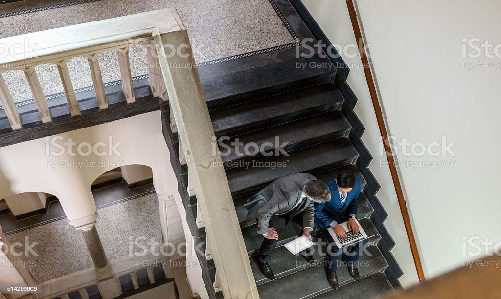 businessmen using digital tablet and laptop on staircase stock photo