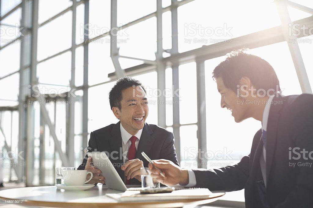 Businessmen using digital tablet in meeting stock photo