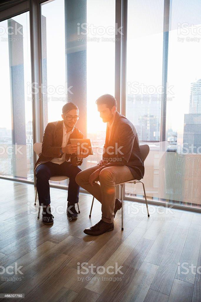 Businessmen using digital tablet in office stock photo