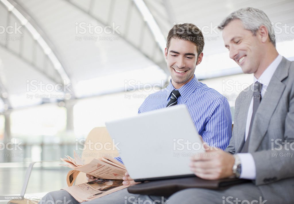 Businessmen using laptop in train station waiting area royalty-free stock photo