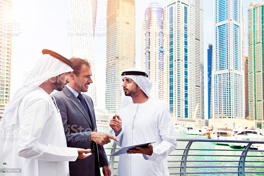 Businessmen using tablet in Dubai Marina. stock photo