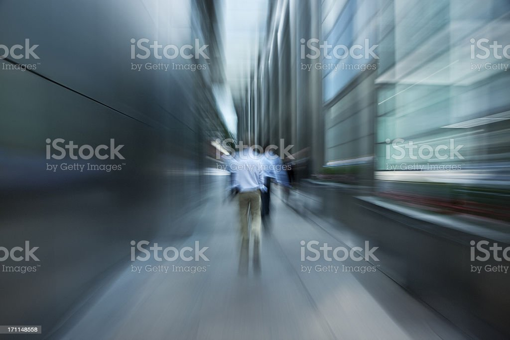 Businessmen Walking Down Futuristic Passage in Financial District royalty-free stock photo
