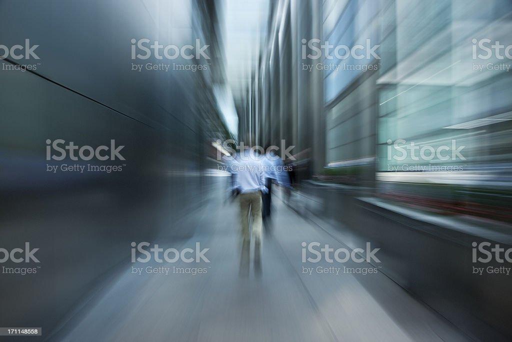 Businessmen Walking Down Futuristic Passage in Financial District stock photo