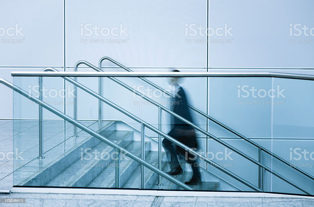 Businessmen walking up stairs blue toned image royalty-free stock photo