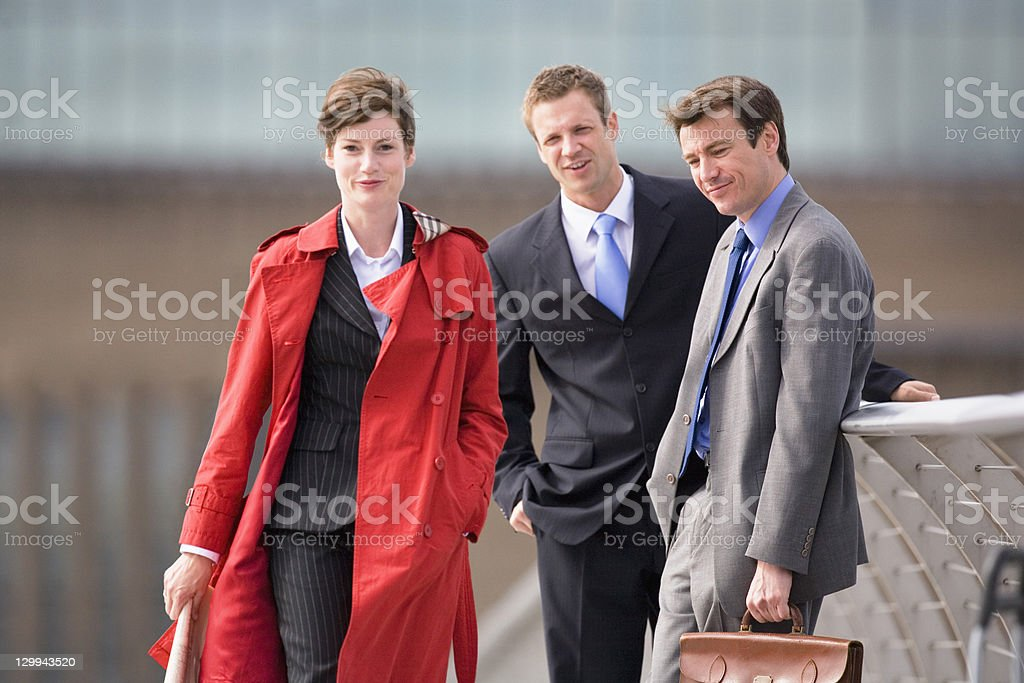 Businessmen watching female colleague stock photo