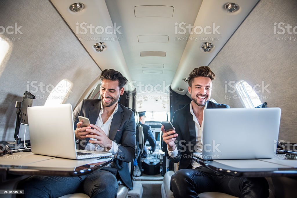 Businessmen with mobile devices inside private aeroplane stock photo