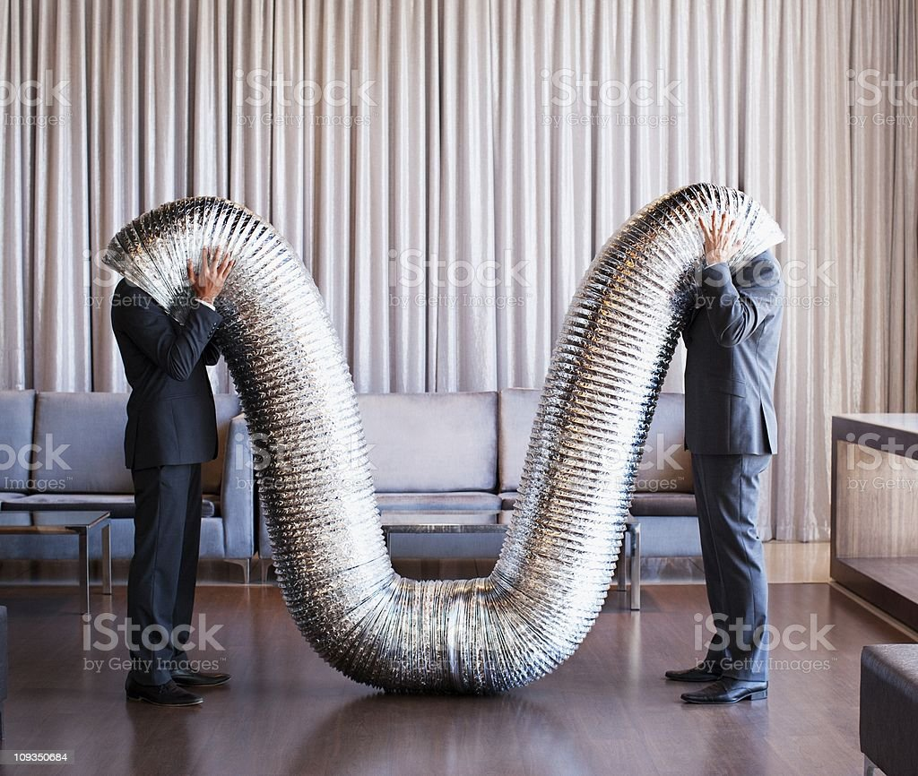 Businessmen with their heads inside metal tubing stock photo