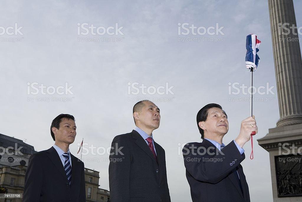 Businessmen with umbrella stock photo