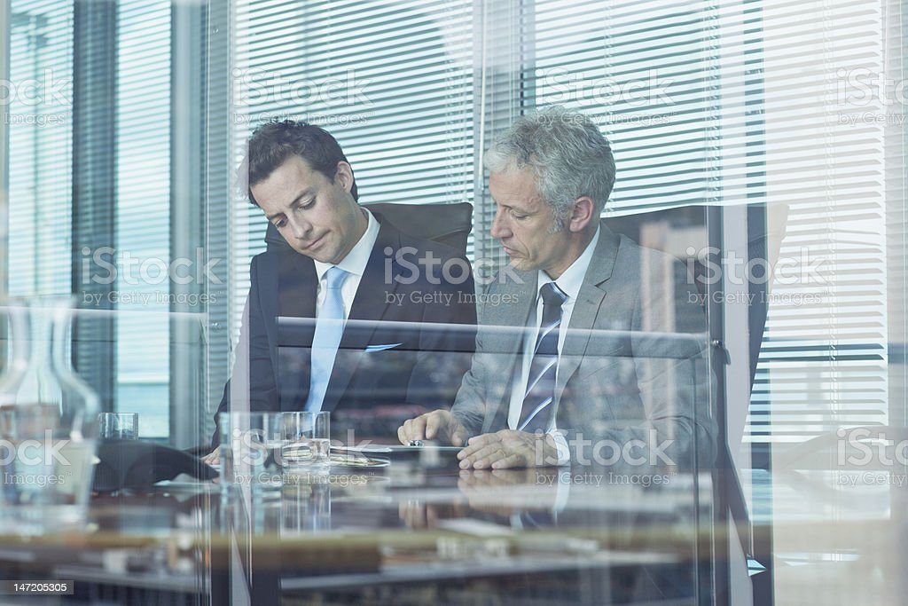 Businessmen working at table in conference room royalty-free stock photo