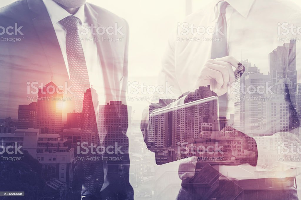 Businessmen working on a digital tablet. stock photo