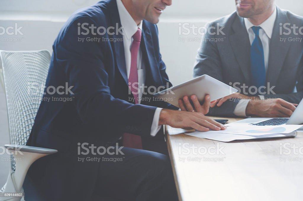 Businessmen working together on a digital tablet. stock photo
