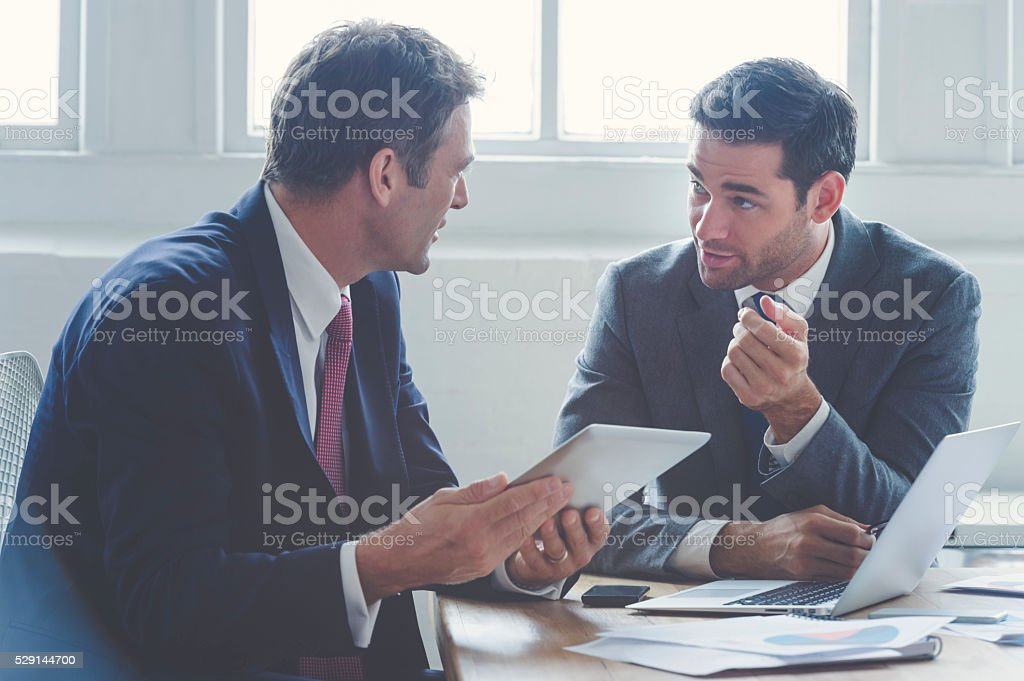 Businessmen working together on a digital tablet. stock photo