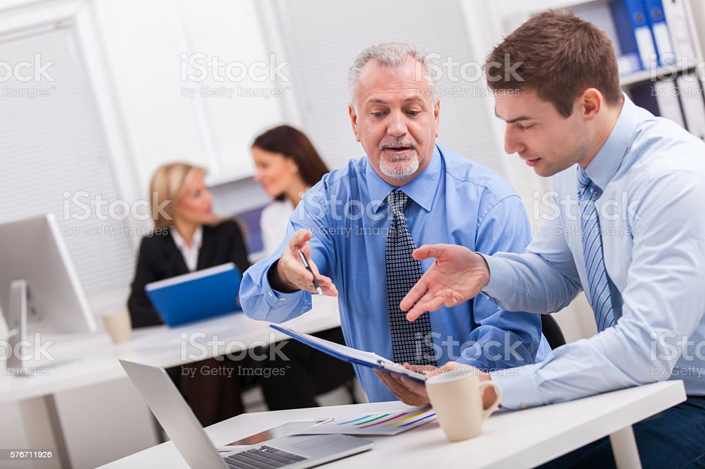 Businessmen working together on a graph in the office. stock photo