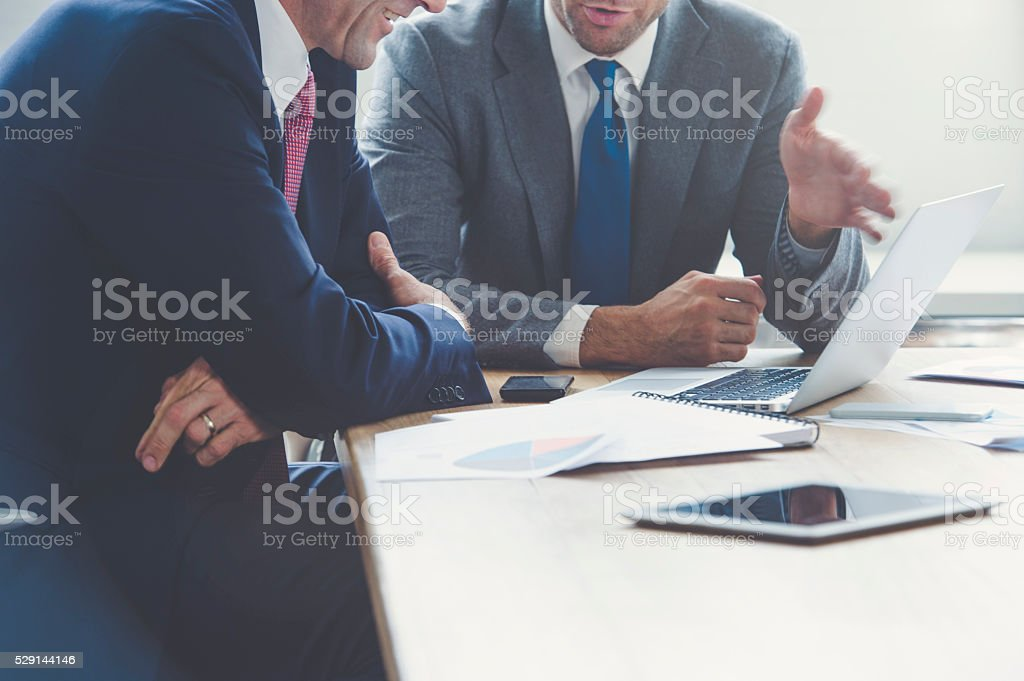 Businessmen working together on a laptop. stock photo