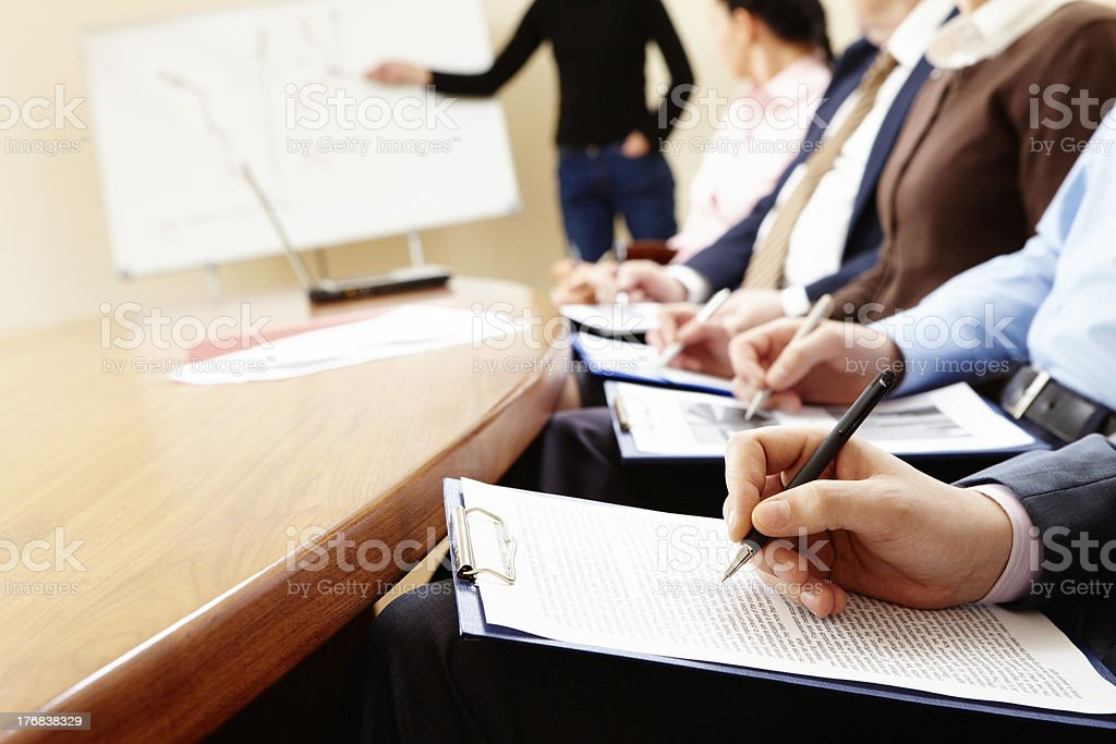 Businesspeople at table with pens and clipboards. royalty-free stock photo