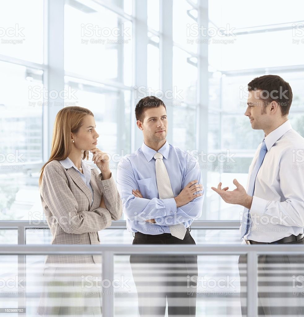 Businesspeople chatting in modern office lobby royalty-free stock photo