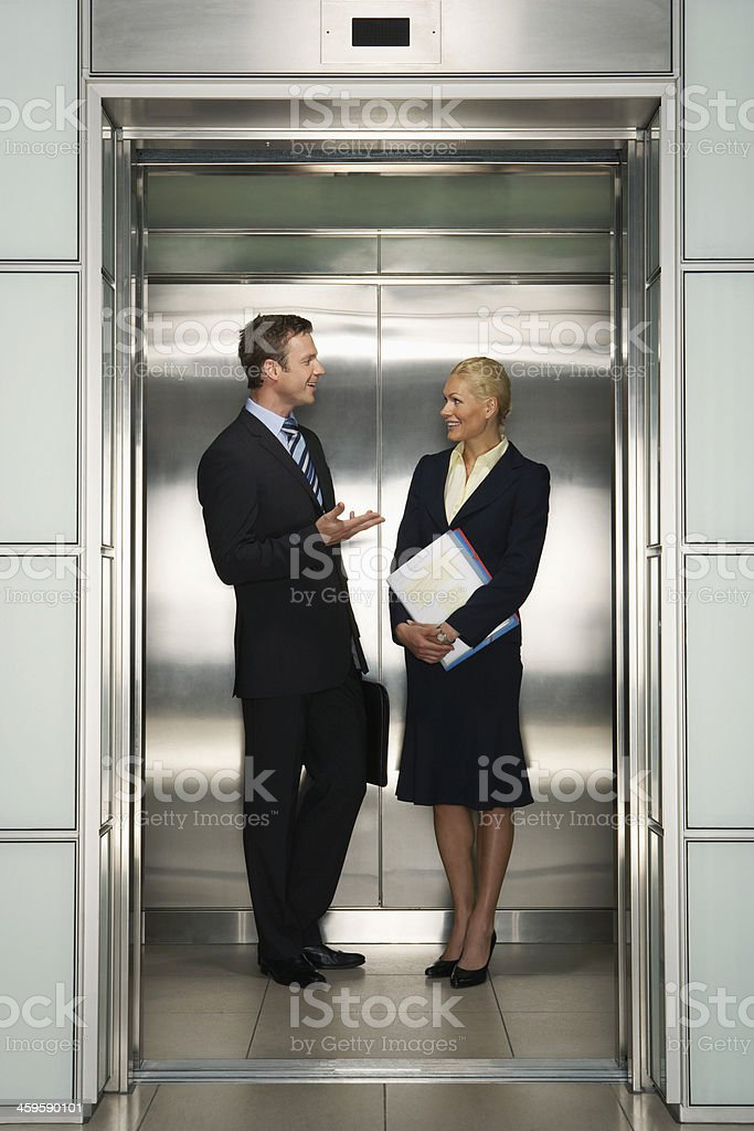 Businesspeople Communicating In Elevator stock photo