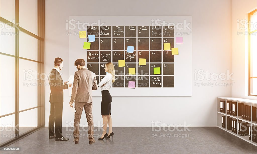 Businesspeople discussing timetable stock photo