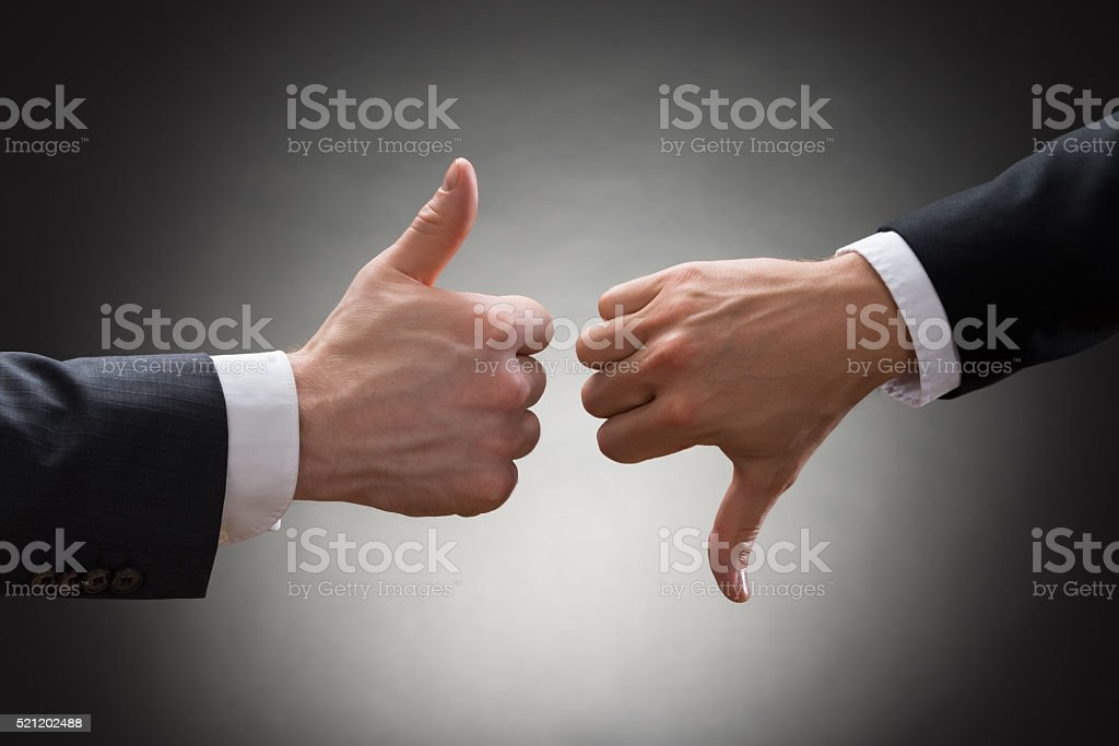Businesspeople Hands Showing Thumb Up And Thumb Down stock photo