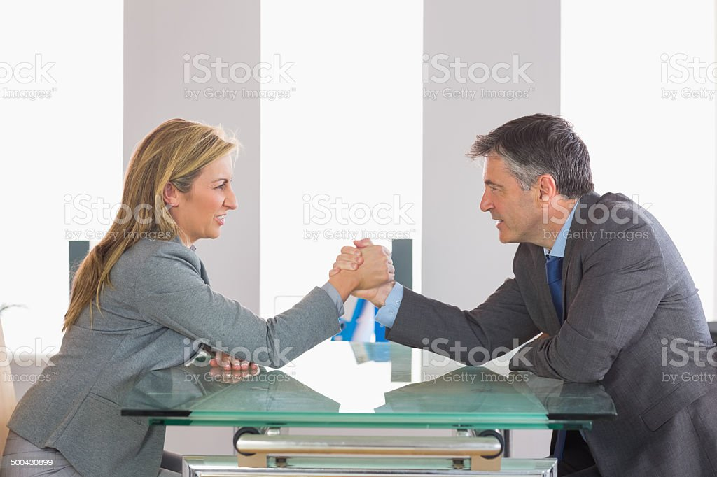 Businesspeople having a showdown sitting around the table stock photo