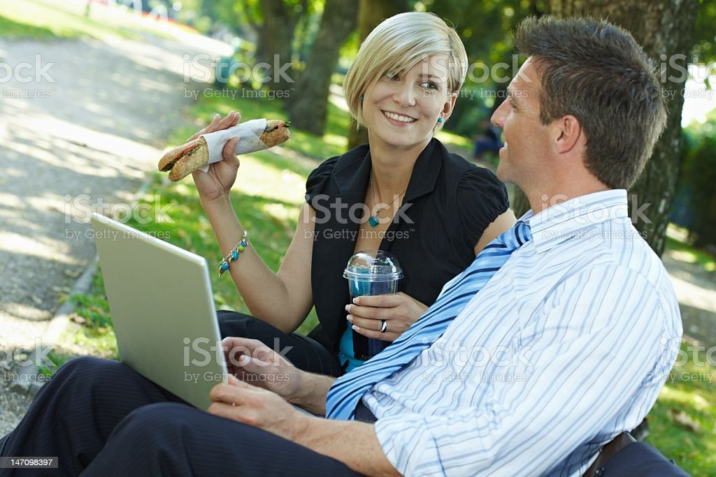 Businesspeople having lunch break in park royalty-free stock photo