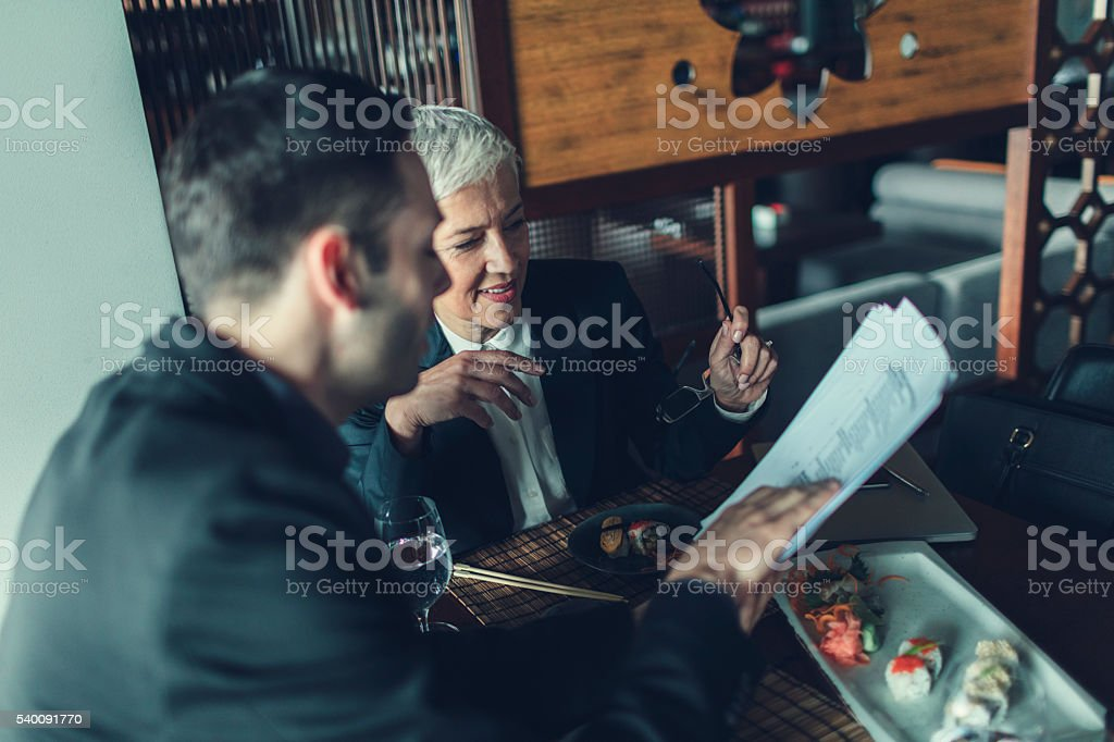 Businesspeople Having Meeting and Lunch In A Restaurant. stock photo