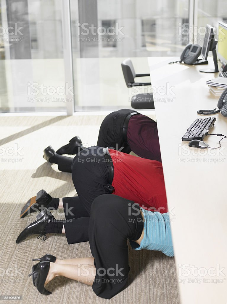 Businesspeople hiding under desk in office royalty-free stock photo