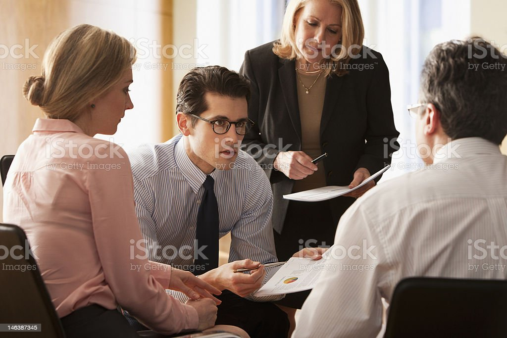 Businesspeople in a meeting comparing notes royalty-free stock photo