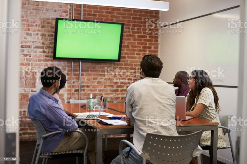 Businesspeople In Meeting Room Looking At Screen stock photo