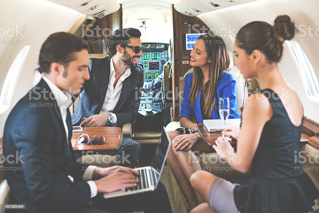 Businesspeople in private jet airplane stock photo