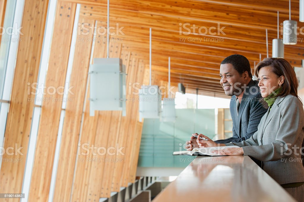 Businesspeople leaning on a railing stock photo