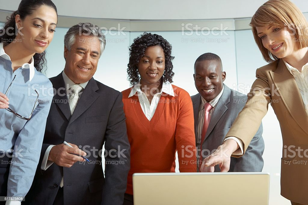 Businesspeople looking at a laptop stock photo