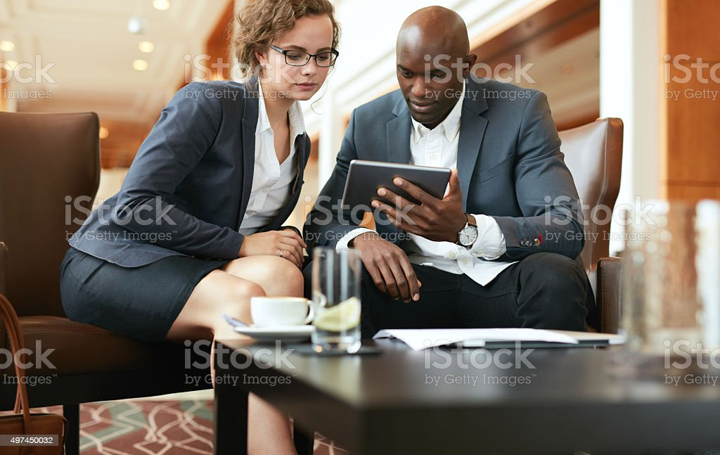 Businesspeople looking at digital tablet stock photo