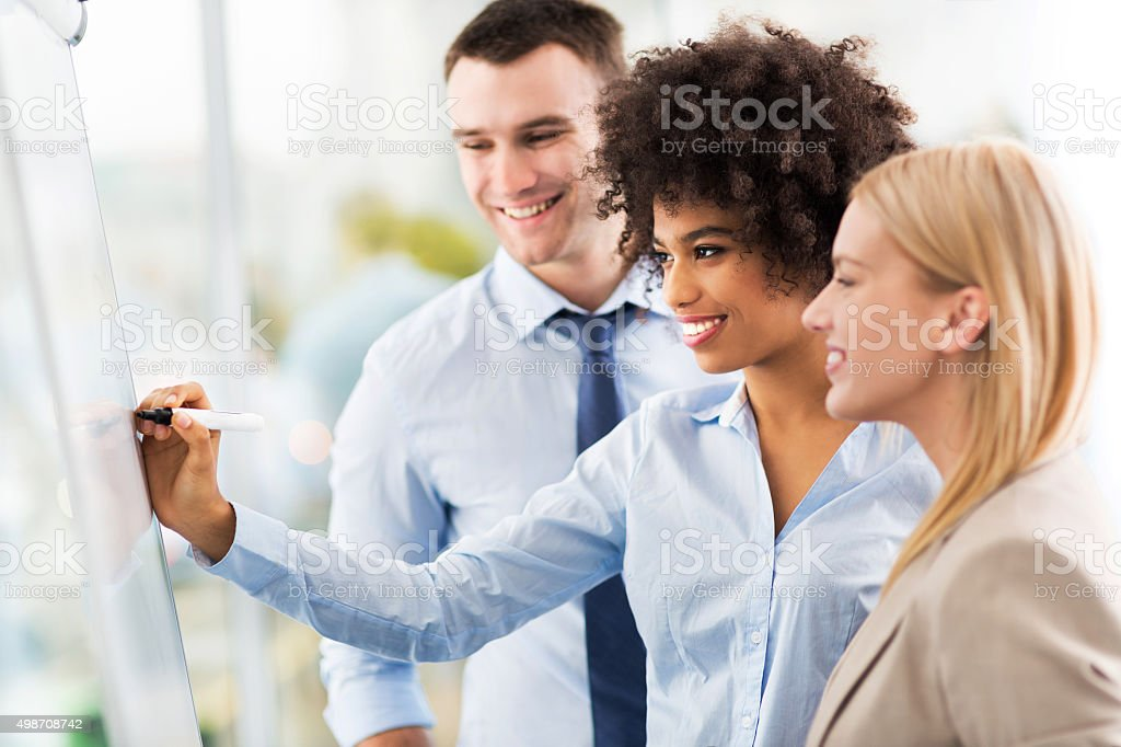 Businesspeople looking at flipchart in office stock photo