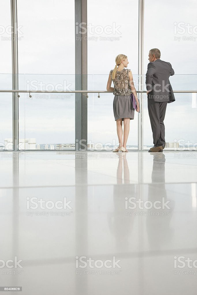 Businesspeople looking out lobby window stock photo