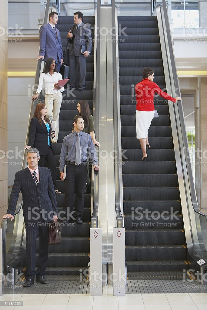 Businesspeople on escalator stock photo