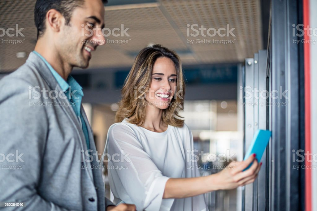 Businesspeople paying contactless on a vending machine at airport stock photo
