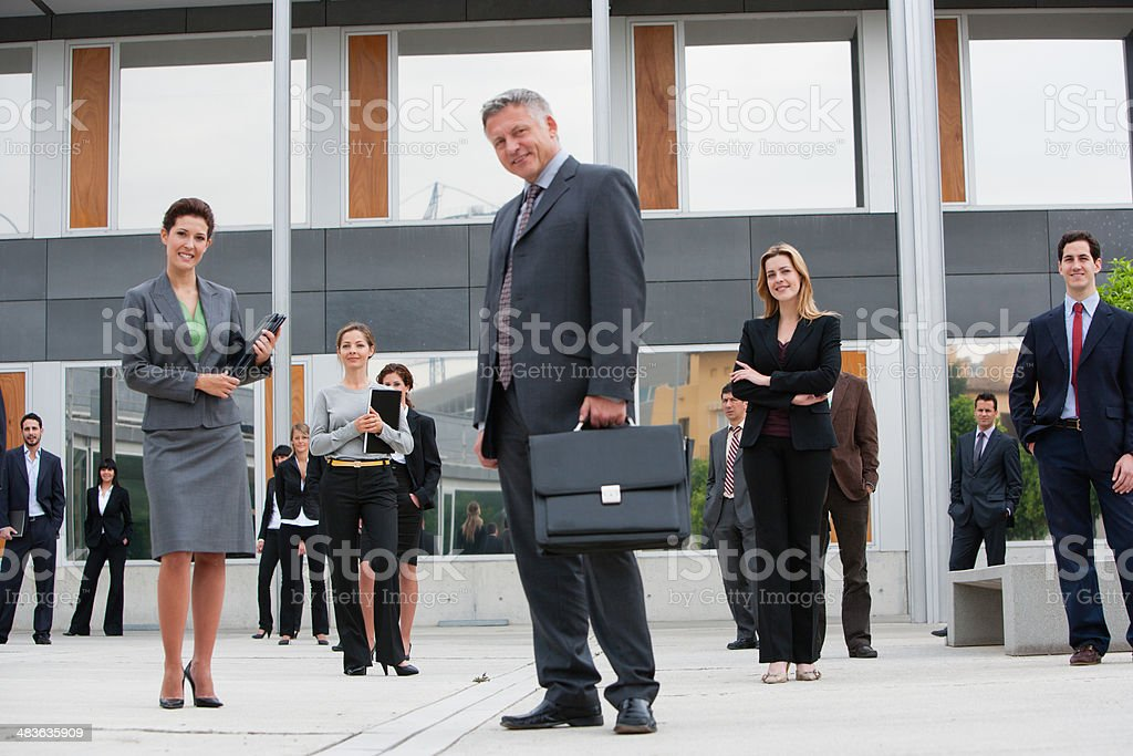 Businesspeople posing in office building courtyard stock photo