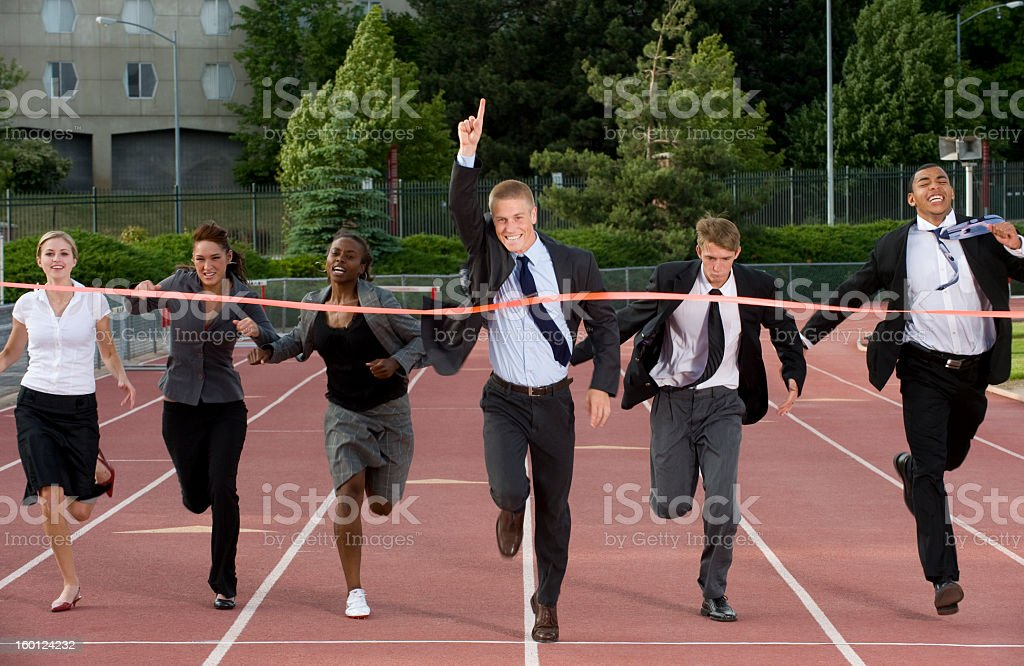 Businesspeople racing on running track to finish line stock photo
