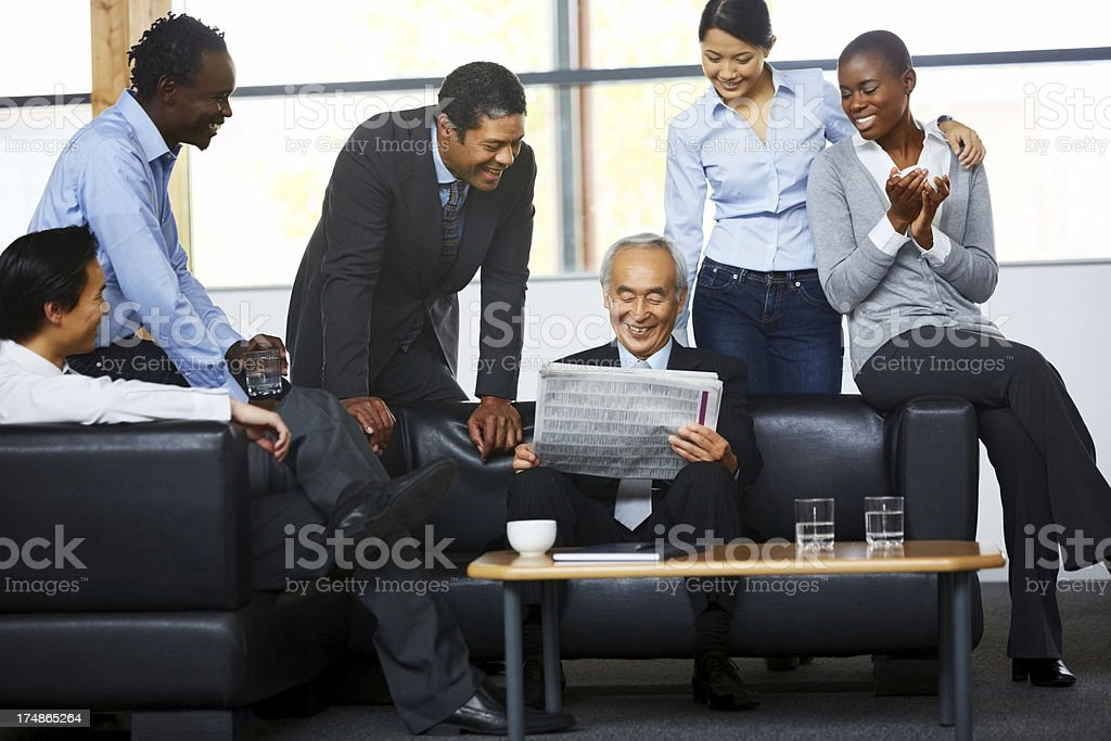 Businesspeople reading their company's achievement article stock photo
