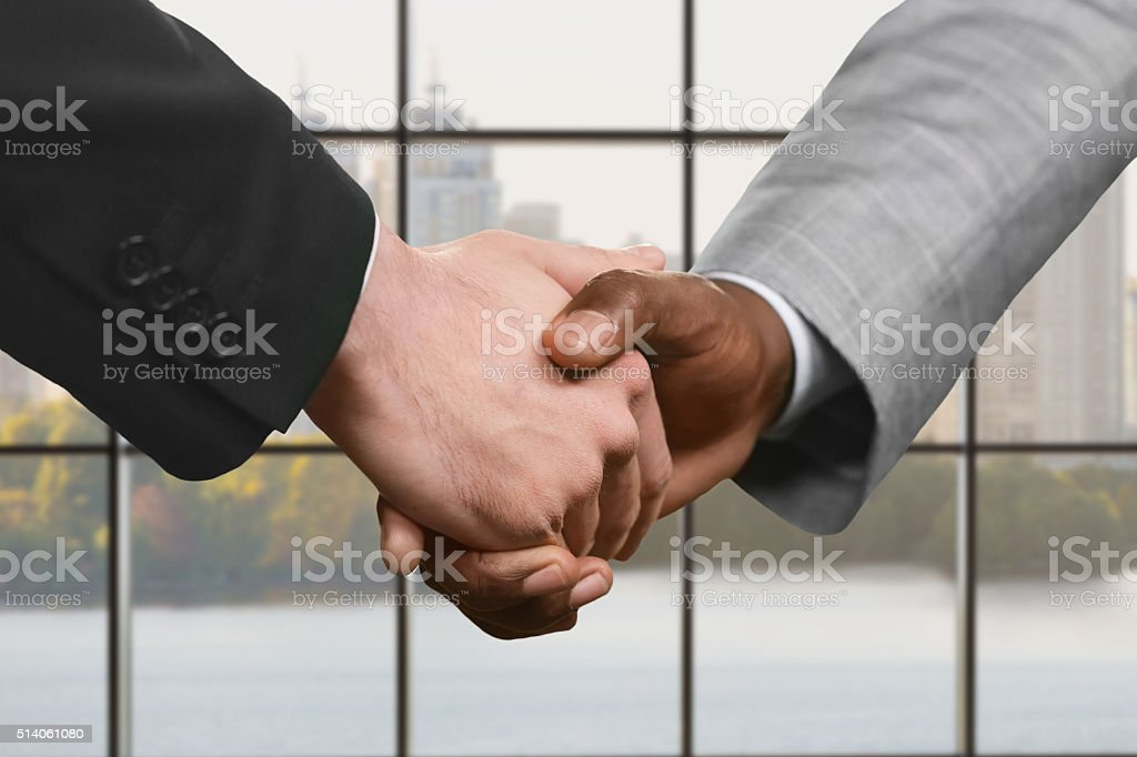 Businesspeople shake hands at daytime. stock photo