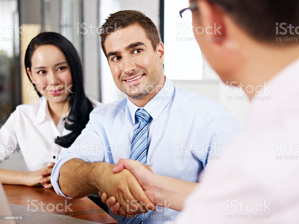 businesspeople shaking hands before meeting stock photo