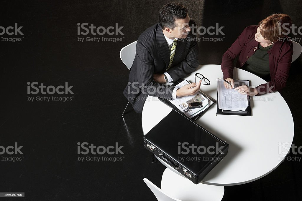 Businesspeople sit at a desk and discuss paperwork stock photo
