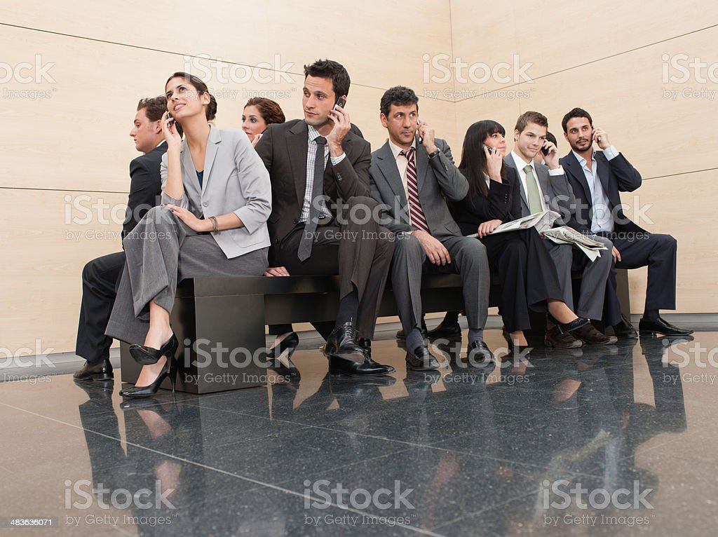 Businesspeople sitting on crowded bench stock photo