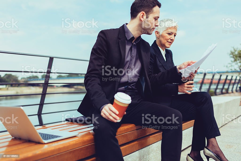 Businesspeople Sitting On The Bench And Examining Documents. stock photo