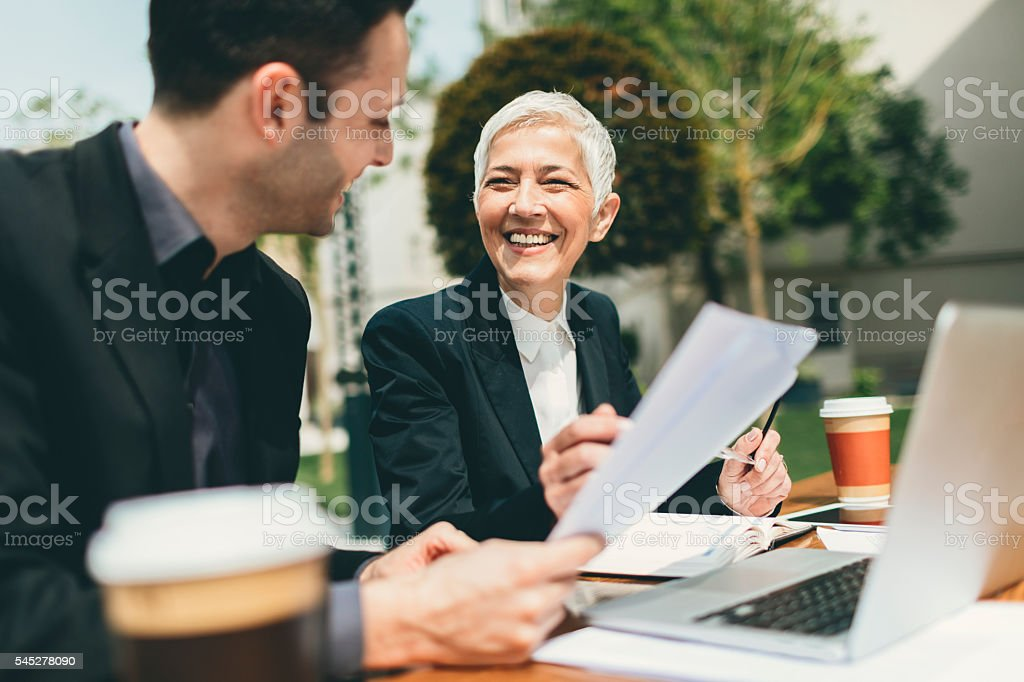 Businesspeople Sitting Outdoors And Using Laptop. stock photo